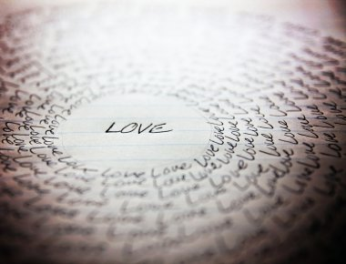 The word love written on a lined piece of school paper in ink with a vignette and a circle of love (very shallow depth of field - focus on the bottom of the word love) stock vector