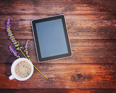 Electronic tablet with coffee and flower