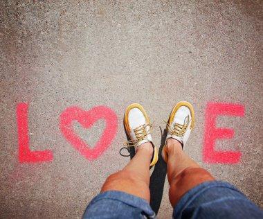 Feet making letter V in word love