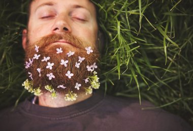 a sleeping hipster lying in tall grass with lilacs in his epic b