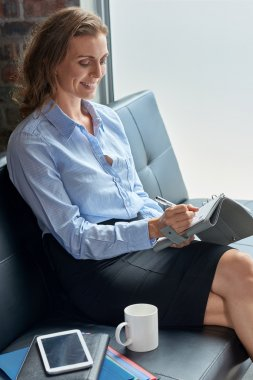 Businesswoman relaxing writing in her diary