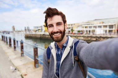 Backpacker man taking selfie on holiday having fun and smiling stock vector