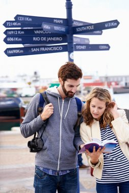 Couple on travel holiday at sign