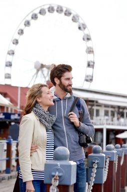 Couple traveling near ferris wheel