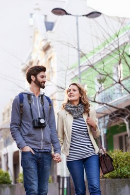 couple walking with camera in city