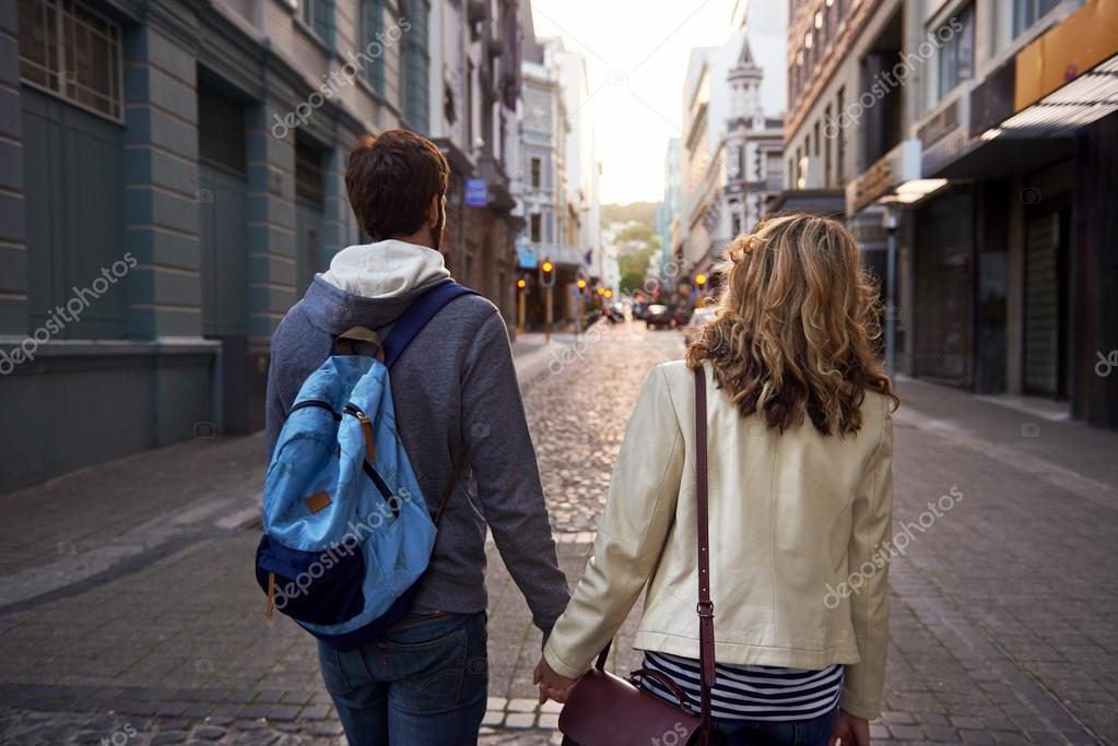 young tourist couple walking street