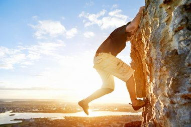 Man rockclimbing up steep mountain