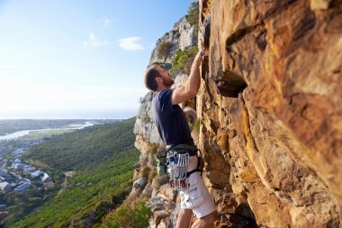 man climbing steep mountain