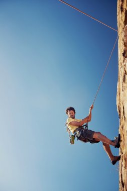 man rapelling down mountain