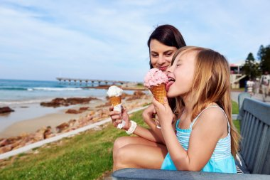 Mom and daughter enjoy ice cream at beach