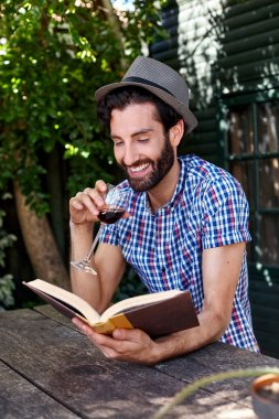 Man outdoors reading book with wine