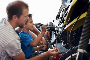 Father teaching son how to use tools