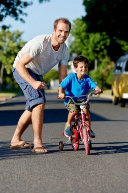 Father teaching son learning to ride bicycle