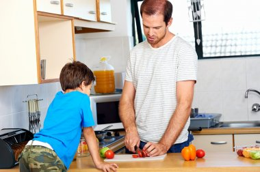 dad in kitchen with son chopping food