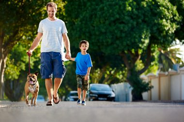 father walking with dog and son