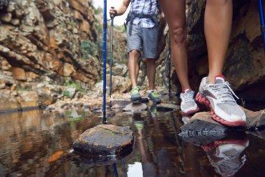 hikers crossing dam
