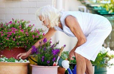 Elderly woman working on flower pot