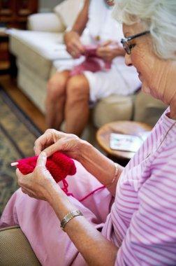 Women friends knitting together inside