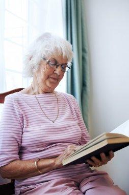 Old lady reading her novel