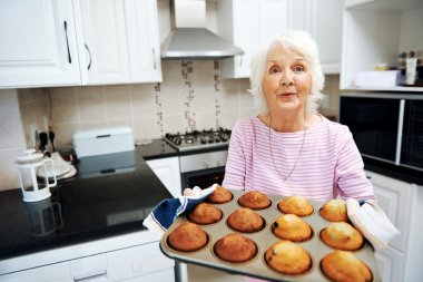 grandmother holding a tray of muffins