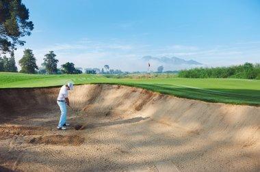 golfer hitting ball from hazard