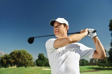 Golfer hitting driver club on course