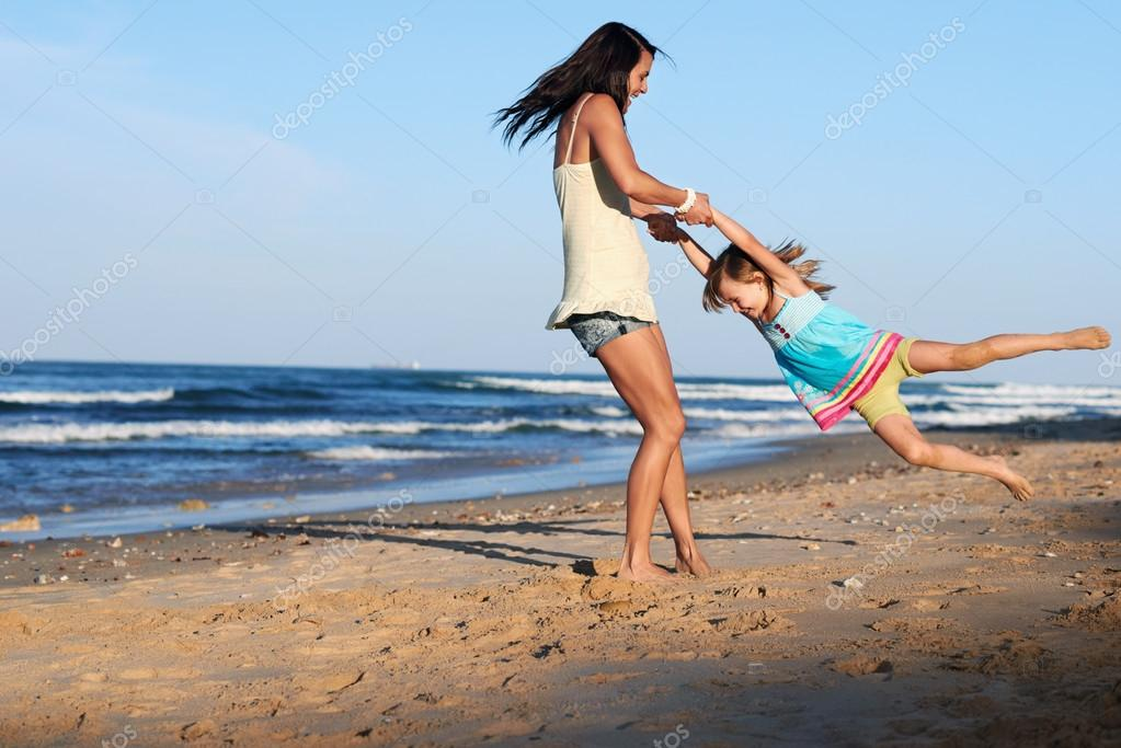 Playful mom and daughter at beach