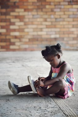 african girl tying shoelace