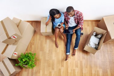 Overhead view of young black african couple with moving boxes in new apartment using modern tablet computer technology stock vector