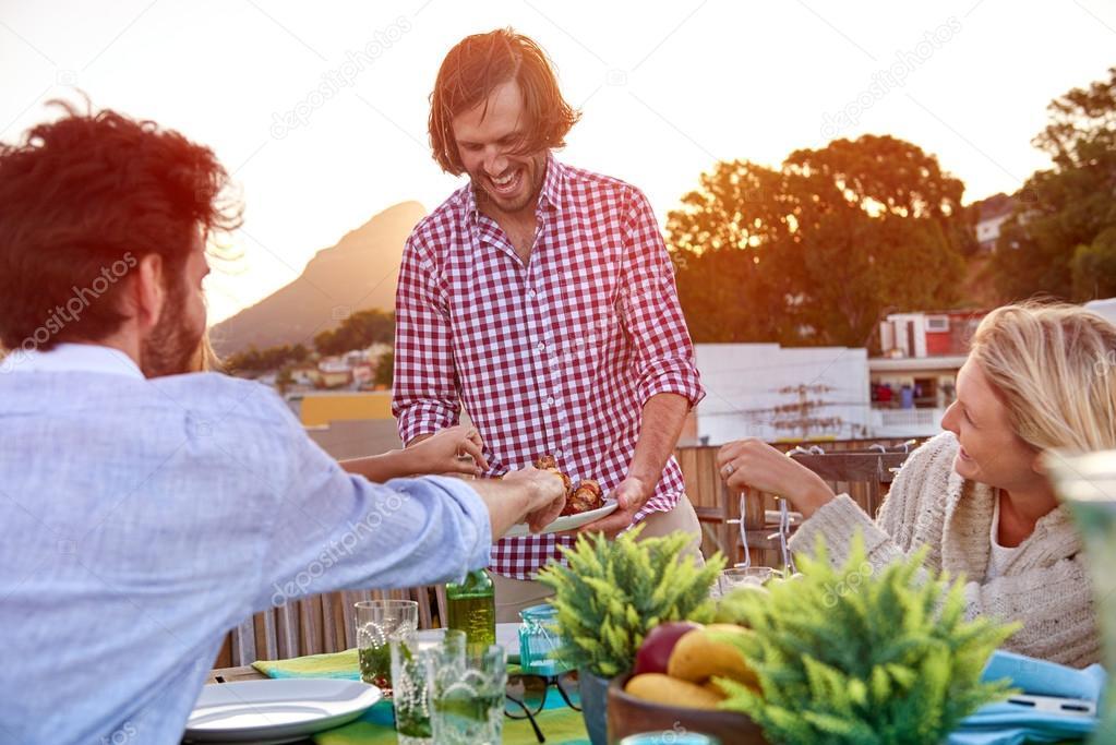 Man serves friends skewer kababs