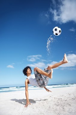 Man doing bicycle kick on beach