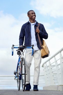african man walking with bike in city