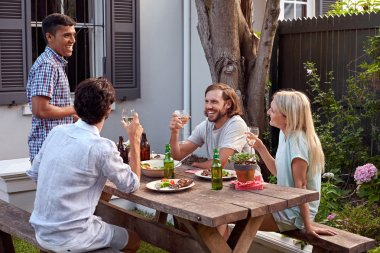 Man toasting speech at friends outdoor