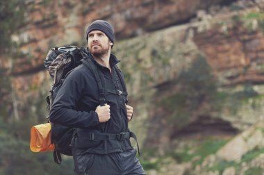 man in mountains with backpack