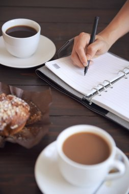 person writing in her diary with breakfast