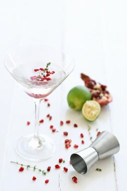 Martini cocktail with lime and pomegranate pips