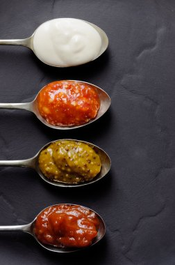 Different types of condiments on spoons