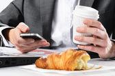 Fényképek man típusú üzleti smartphone a reggeli elfogyasztása közben
