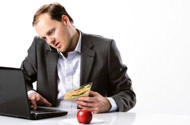 Multi tasking businessman works through lunch