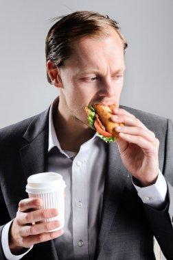 Busy businessman eating takeaway sandwich