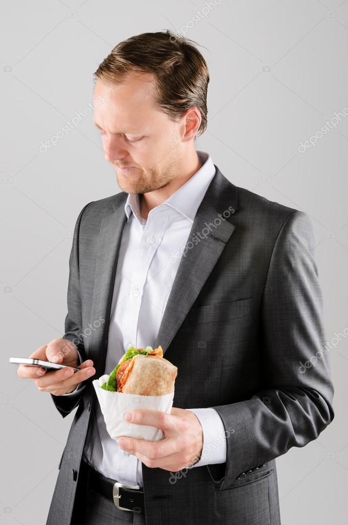 Frowning business man with lunch and mobile phone