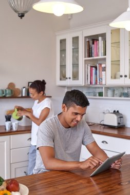couple with coffee and tablet computer in kitchen