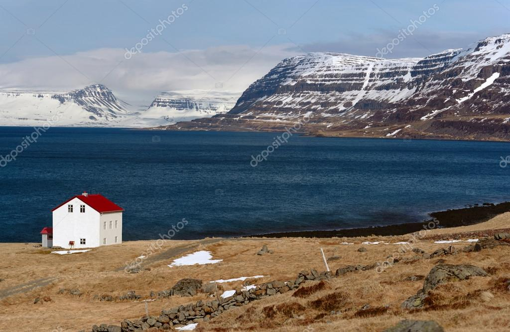 cabin near lake and snowcapped westfjords in icelandic mountains