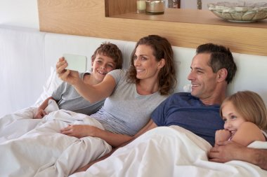 mom taking a family selfie in bed