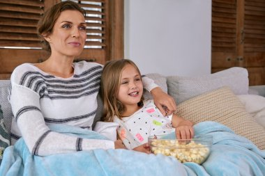 mother and daughter watching movies and eating popcorn