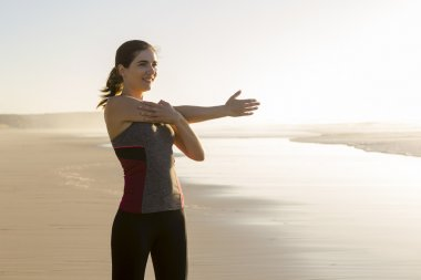 Woman making stretching exercises in the beach