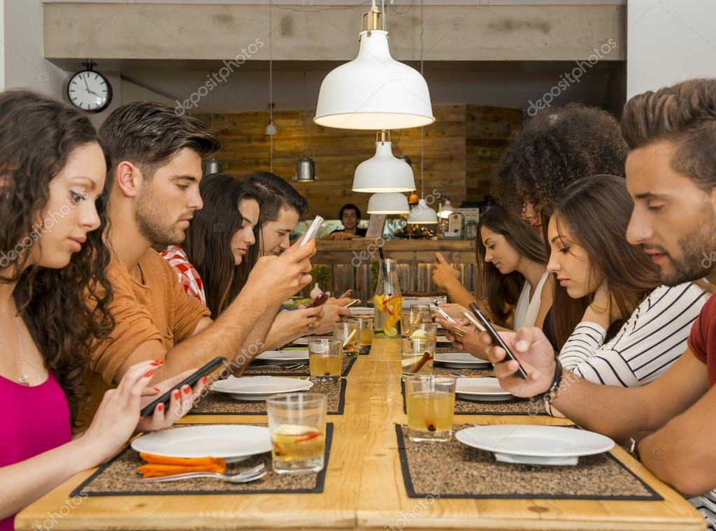 friends at a restaurant  occupied with cellphones