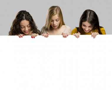 Studio portrait of three girls holding and showing something on a cardboard stock vector