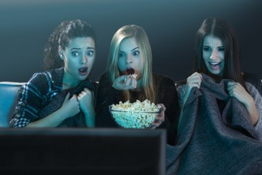 Teenage girls watching horror movie