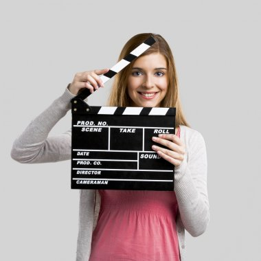 Beautiful blonde woman holding  a clapboard, isolated over gray background stock vector